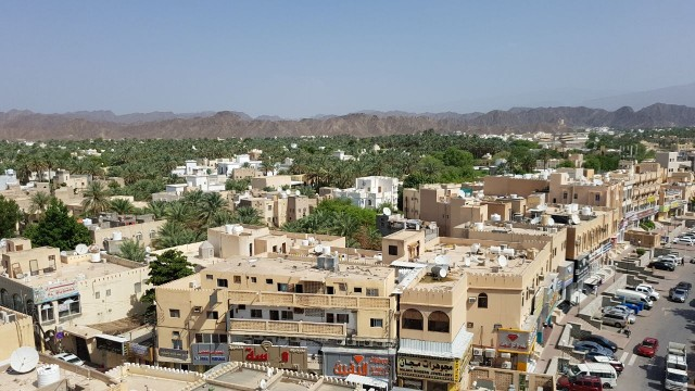 A Great Image view of Nizwa city from a high building, showing the mountains bordering the city also the palms in green color looks very amazing